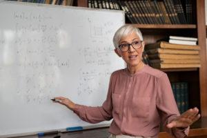 Portrait of senior professor explaining math formulas. Mature f